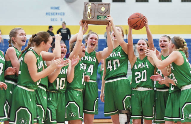 Anna's Kipyln Rowland, center, holds up the team's Division III regional championship trophy after defeating Cincinnati Purcell Marian on Saturday at Springfield High School.