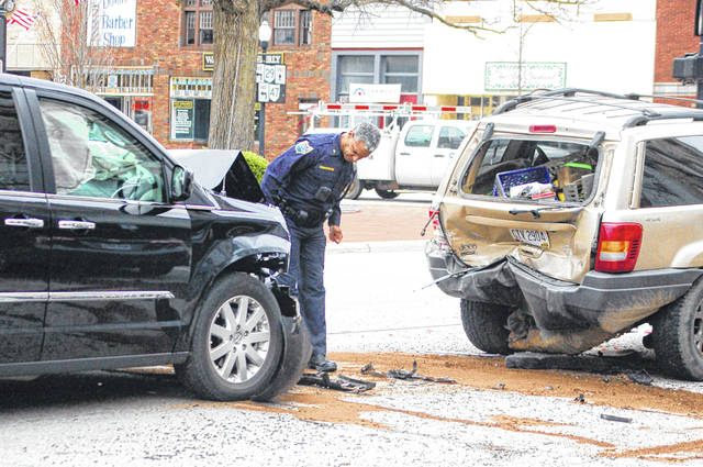 Sgt. Tony Cunningham, of the Sidney Police Department, inspects a two-vehicle crash on South Ohio Avenue just north of the Court Street intersection shortly after 2 p.m. Monday.