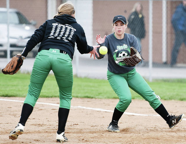 Anna's Maggie Steifel, left, tosses the ball she fielded to Brielle Collier as Collier makes her way to first base during a Shelby County Athletic League game on April 30, 2019 in Anna. The OHSAA officially announced the cancellation of spring sports on Tuesday.