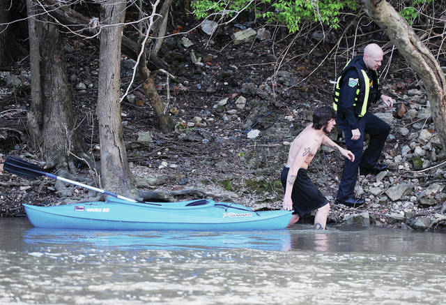 A man pulls a kayak behind him as he and a Sidney Police officer walk back towards the Stolle Bridge soon after several people fell into the Great Miami River on Monday, April 27.