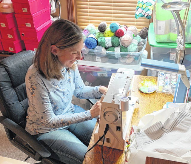 Emilie Britton, of New Bremen, sews a mask at her home on Wednesday, April 1. She organized a group of volunteers to make over 4,000 masks to help meet the need of the medical community due to the COVID-19 pandemic.