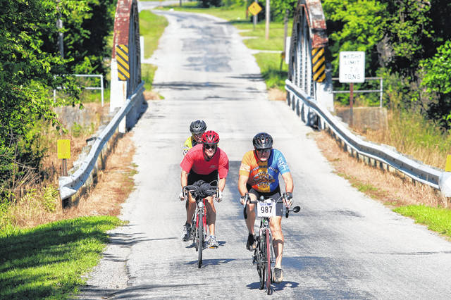 Great Ohio Bicycle Adventure riders make their way over a bridge on Long Judson Road after leaving Grand Rapids and making their way into Bowling Green on June 24, 2015. GOBA 32, which was scheduled to start and finish in Sidney in June, has been canceled for 2020 but will return with the same itinerary in 2021.