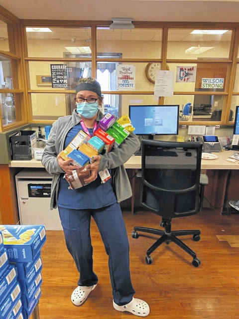 """Alys Fleckestein, RN, nurse manager of Acute Care and CCU at Wilson Health shows off an arm full of various boxes of Girl Scouts cookies that were donated Monday morning, April 20, by Girl Scouts Troop 237. """"We are beyond grateful for the donation of cookies from our local Girl Scouts troop,"""" said Margo O'Leary, director of marketing and communications at Wilson Health. """"Thank you for helping us to provide some relief and support to our frontline staff during this time."""""""