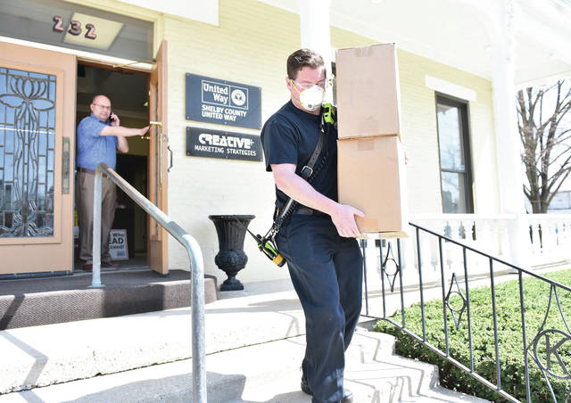 Sidney Firefighter Chance Guisinger, of Anna, takes a load of Hazmat suits away from the Shelby County United Way Office. Watching is United Way President and C.E.O. Scott Barr.