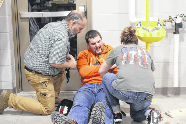 Kevin Stanley, an intervention specialist and transportation supervisor, left, and Misty Trask, a janitor, right, respond during advanced level active shooter preparedness training for Arcanum-Butler Local Schools on Feb. 19. Playing a victim in the scenario is Collin Habel, a member of the Sidney Fire Department.