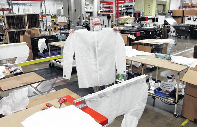 Joe Blake, president of Industry Products Company, of Piqua, displays an isolation gown made through a partnership with Premier Health and FastLane.