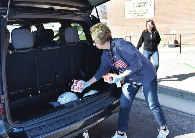Northwood Intermediate School Paraprofessional Jolene Krebehenne, left, and School Librarian Amy Wildermuth, both of Sidney, put school lunches into a minivan at Northwood Intermediate School on Thursday, April 2. The school is handing out school lunches to students while the schools are closed due to COVID-19.