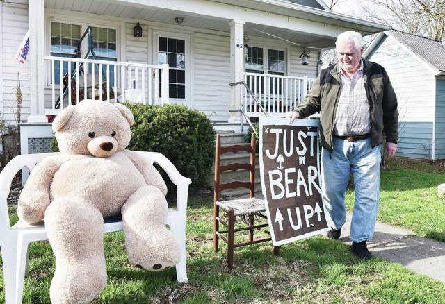 "On Friday, April 3 Joe Robinson, of 105 E Bennett St., puts out a giant stuffed bear and a sign next to it that reads ""Just Bear Up."" Robinson said the bear was in his bedroom just taking up space when he got the idea to use it to cheer up kids driving buy. Robinson's wife, Vicki Robinson drew the letters for the sign."