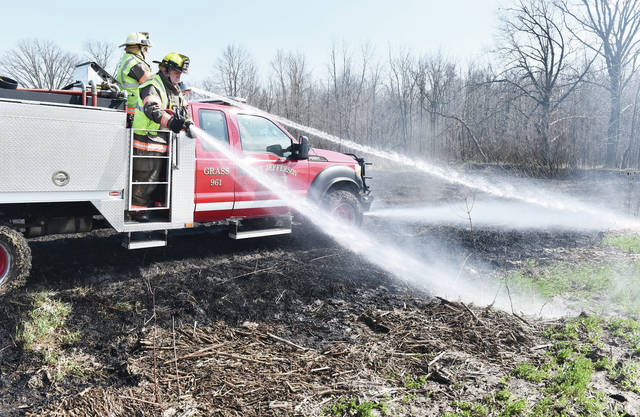 Port Jefferson firefighters spray down hotspots on a field that caught fire from an adjacent controlled burn that was taking place behind a house on the 10000 block of Lochard Road around 3 p.m. on Friday, April 3.
