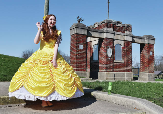 "Dressed as Belle from the movie ""Beauty and the Beast,"" Olivia Breinich, 12, of Sidney, daughter of Amy and Benji Breinich, waves at passing motorists from the front of Julia Lamb Field on Friday, April 3. Olivia waved to people to brighten up their day. Olivia has been reading to kids online during the COVID-19 lockdown. She has dressed as Disney princesses while reading such stories as ""The Very Hungry Caterpillar,"" ""Frozen"" and ""Beauty and the Beast."" House bound kids can watch her read for free on Facebook at https://www.facebook.com/viabeeproductions/."