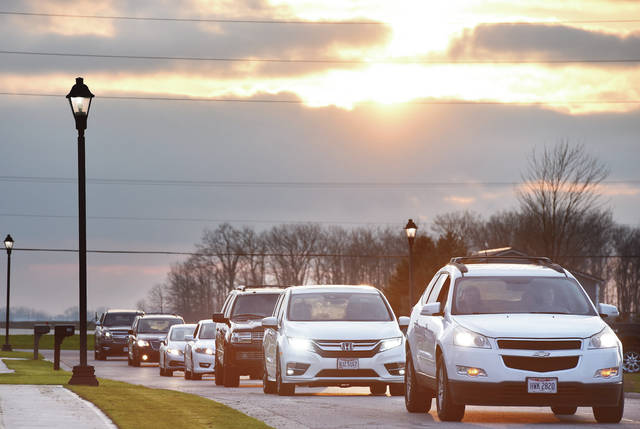 Vehicles drive down Oakwood Street in Russia shortly after 7:30 p.m. on Sunday, April 5, in a tribute to Randall Marchal, of Russia, who died Saturday.