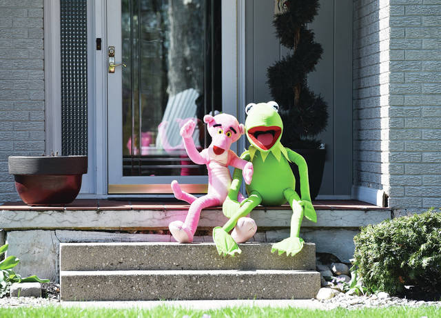 The Pink Panther and Kermit the Frog sit on the front porch of a house on Port Jefferson Road. The two were taking in the sun on Monday, April 7.