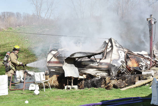 A Sidney Firefighter puts out a travel trailer fire out behind a house at 1978 Miami River Road at around 5 p.m. on Wednesday, April 8. The trailer was almost completely destroyed by the fire. The Lockington Volunteer Fire Department and Shelby County Sheriff's Office also responded to the scene.
