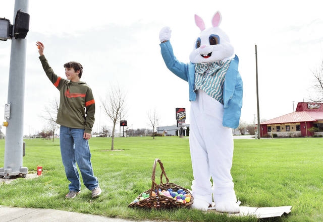 The Easter Bunny waves to cars as they drive past Pizza Hut along Amsterdam Road in New Bremen on Saturday, April 11. Helping wave to cars is volunteer Dalton Fink, 12, of St. Marys, son of Ashley and Dan Fink. Pizza Hut was going to have an Easter Egg hunt before the coronavirus made for a change of plans. Their pizza delivery workers have been delivering some of the eggs with ordered pizzas that were originally meant for the egg hunt.