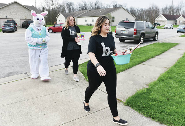 The Easter Bunny along with B-Squared Hair Studio employee Carmen Gephart and B-Squared Hair Studio owner Bethany Bolton, both of Sidney, deliver Easter baskets to a house in Sidney on Saturday, April 11. B-Squared Hair Studio sold over 100 Easter cookie kits to raise the money to buy 70 Easter baskets. With the Easter Bunny they delivered the baskets to 25 households in Sidney that have children that are less fortunate. B-Squared Hair Studio was shut down along with all other hair salons by a state-mandate to slow the spread of the coronavirus.