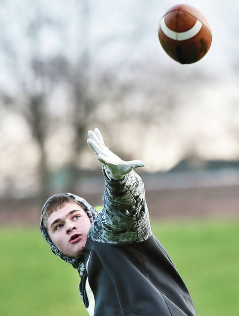 "Wesley Davidson, 16, of Sidney, son of Chad and Amanda Davidson, practices his running one-handed catch with help from his dad at Julia Lamb Field on Tuesday, April 14. Davidson is an Anna High School varsity football player whose team won the Division VI state championship last year. When asked how the coronavirus had effected his sport Davidson said, ""We can't practice as a team right now. I wish we could all be together getting ready for the next season."""