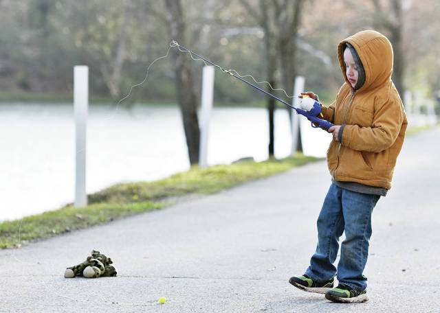 Jaxson Latimer, 4, of Sidney, son of Ty Latimer and Kendra Ellis, practices his fishing skills at Tawawa Lake on Wednesday, April 16. Jaxson caught himself briefly by his right coat sleeve but was able to quickly free himself.