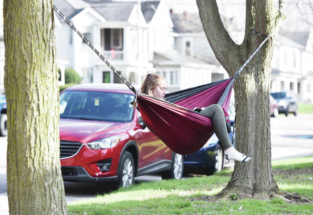 "Amanda Jaycox, of Sidney, reads ""Gerald's Game"" by Stephen King while sitting in a hammock along South Main Avenue on Saturday, April 18. Jaycox is currently interning at Emerson Climate Technologies. She is a corrosion engineering major at the University of Akron."