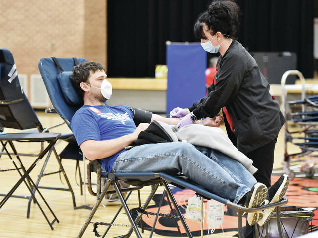 "Michael Dillon, of Minster, has blood drawn by Team Leader Crystal Gudell, of Greentown, Ind., during a community blood drive held in the Minster High School gym on Monday, April 20. The blood drive was hosted by the Auglaize County Farm Bureau and worked by the American Red Cross. Everyone was required to wear masks, have their temperatures checked and hands sanitized before entering to prevent the spread of the coronavirus. Dillon has given blood since he was in high school. When asked why he gives blood Dillon said his ""son had heart surgery at one point in his life and that has continued to motivate me."""