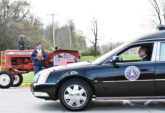 Jackson Center Mayor Scott Klopfenstein waves goodbye to his lifetime friend Ivan E. Zorn as Zorn's hearse drives past in Jackson Center on Monday, April 27. Klopfenstein clutched the old wooden show stick and halter he used as a kid when Zorn helped teach him to show steers at the Shelby County Fair in the 1960's. Klopfenstein's family would buy their steers from Zorn's father Ernest A.R. Zorn. Klopfenstein described Zorn as a big brother/father like figure to him and a pillar of the community.