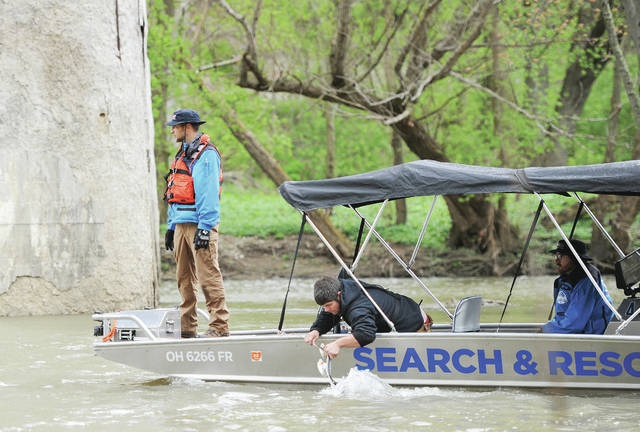 A search and rescue vehicle equipped with computer monitors passes under the Big Four Bridge as the search for a missing man continued on Wednesday, April 29. The man was one of several who fell into the Great Miami River in an accident near Stolle Bridge on Monday, April 27.