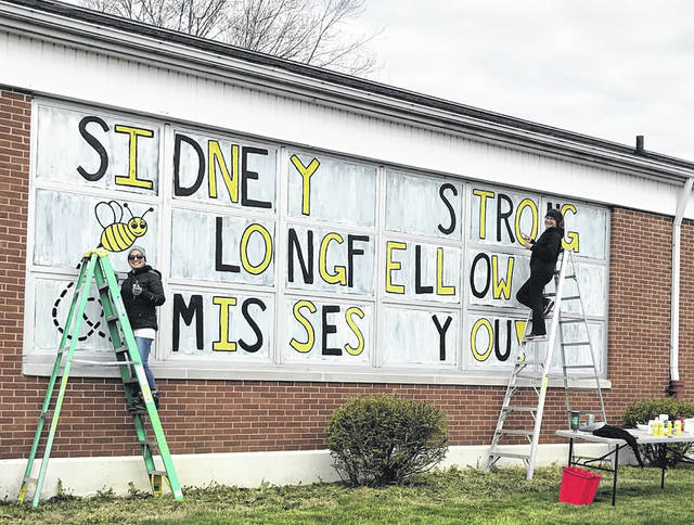 Longfellow Primary staff members Cristina Jenkins, left, and Cindy Biddle right finish up a window mural at Longfellow.