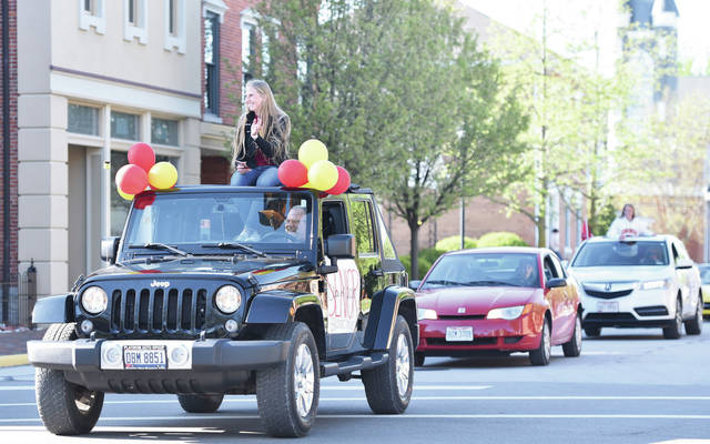 New Bremen senior Brooke Dicke waves from the top of a Jeep while taking part in a parade through New Bremen in honor of the New Bremen class of 2020.