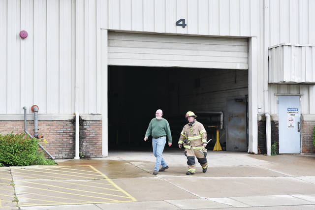 A Sidney firefighter, right, and an employee emerge from Ross Aluminum Castings after a large explosion from inside the building shook nearby houses on Friday, May 29.