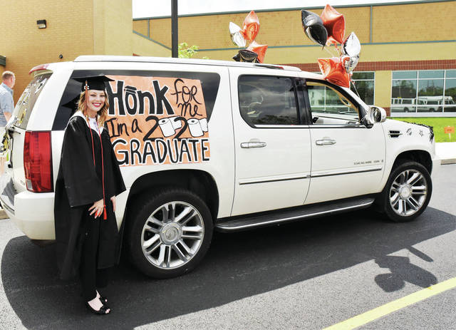 Kylie Hartle stands by the SUV she was soon to ride in the Jackson Center graduation parade on Sunday, May 24.