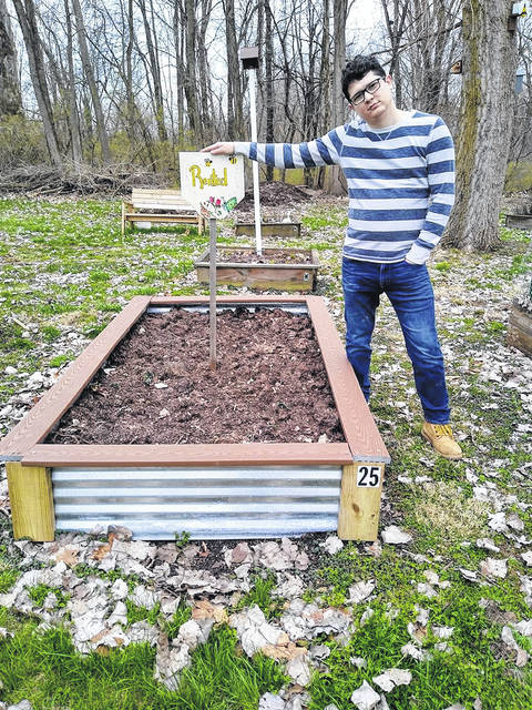 Lee Elsass stands next to one of the raised beds available to rent at the Peoples Garden.