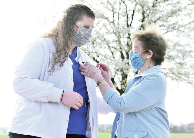 Kaitlin Gillman, left, of Sidney, has her nursing pin attached to her shirt by her grandma Casey Wehrle, a resident at Ohio Living Dorothy Love, in a pinning ceremony held outside Dorothy Love on April 24 . Wehrle wore her own nursing pin that she received in 1955. Gillman graduated from Rhodes State College.