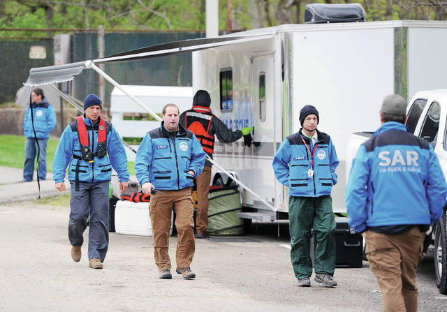 Search and rescue workers walk by their trailers set-up in the parking lot next to the west side of Stolle Bridge on Thursday, April 30. A helicopter could also be seen flying up and down the Great Miami River. Rescue workers have been looking for a man who fell into the river on Monday, April 27, after going over the dam next to Stolle Bridge along with three other people. The search continued until after noon Thursday. OSP's helicopter, Sidney Firefighters and members of the Ohio Department of Natural Resources will continue the search Friday as long as weather and river conditions permit.
