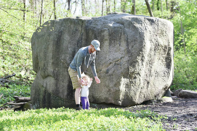 Garrett Gatton, left, walks with his daughter Tirzah Gatton, 3, both of Lima, next to Big Rock at Tawawa Park on Friday, May 1. The two were seeing Big Rock for the first time having never been to Tawawa Park before. Their family was having a picnic by the grove adjacent to Big Rock. Tirzah is also the daughter of Lydia Gatton.