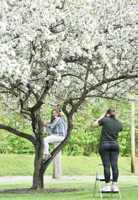Ashley Roush, left, 17, daughter of Karen and Darrin Ike, sits perched in a flowering tree as her sister Allison Roush, both of Sidney, takes her photo on Monday, May 4, at Riverside Park. It took some good natured cajoling to get Ashley Roush into the tree after her sister had just made her climb a different tree. Ashley Roush will pick her favorite photo to use as her senior photo at Fairlawn Local Schools next year. Ashley Roush is just finishing her junior year. Allison Roush just finished her freshman year at Ohio University.