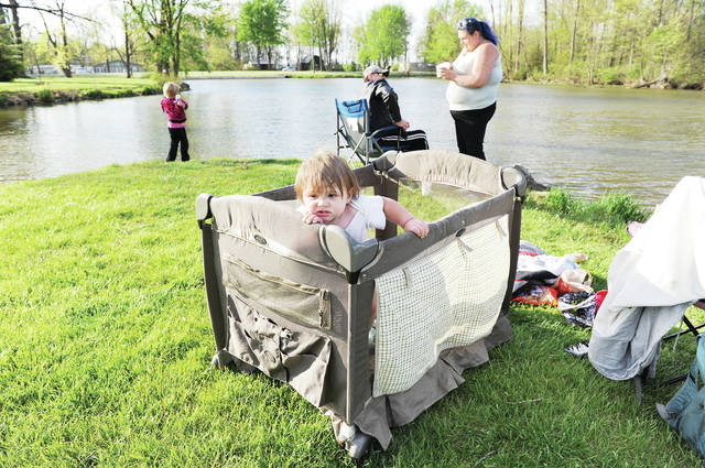 Spencer Newport, 11-months-old, tries to climb out of his Pack 'n Play while his family, left to right, sister, Elizabeth Rigel, 6, stepdad, James Branscum, and mother, Tamira Langley, all of Sidney, fish behind him at Lake Loramie State Park on Thursday, May 7. Branscum is also the stepdad of Elizabeth and Langley is her mother. The park was full of people fishing, boating and walking.