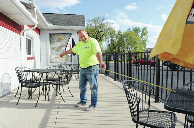 Cruizer's owner Steve Young, of Russia, shows how far apart he moved tables on his back patio in preparation for customers, whom he will serve on Friday when restaurants in Ohio will be able to serve people seated outside.
