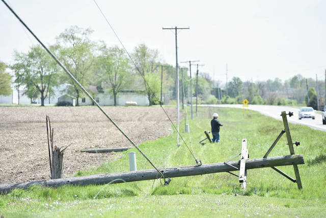 A DP&L worker responds to where at least 3 utility poles were knocked down by a tractor along the 10300 block of State Route 25a around 2:30 p.m. on Wednesday, May 13.