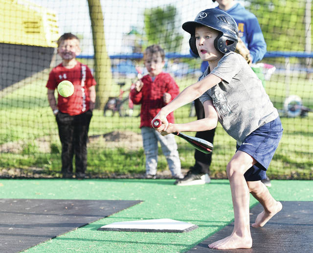 Patrick Borchers, 6, of Russia, son of Dane and Rachel Borchers, practices his swing in a batters cage next to a ball diamond behind Russia Local School on Tuesday, May 12. Borchers is working on his skills with family members just in case the Russia Community Junior Athletic Association still has a baseball season this summer.