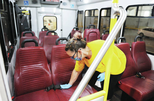 Shelby Public Transit driver Kathy Barhorst, of Sidney, cleans a transit bus' seat with disinfectant wipes at the Shelby Public Transport office on Thursday, May 14. Barhorst wipes down whatever bus she is driving twice during her shift.