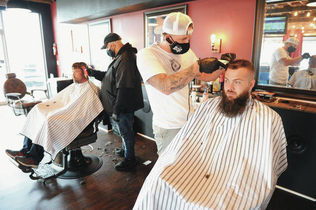 Seated, Robert Stiney, left, of Sidney, has his haircut by Mica Cupp, of Troy, as JC's Barbershop owner Jacob Cornett, of Sidney, cuts the hair of Jacob Pennington, of Celina, on the first day of JC's Barbershop reopening on Friday, May 15. Like the rest of the barbershops and salons in Ohio JC's had been closed to stop the spread of COVID-19 until Friday when they were allowed to open.