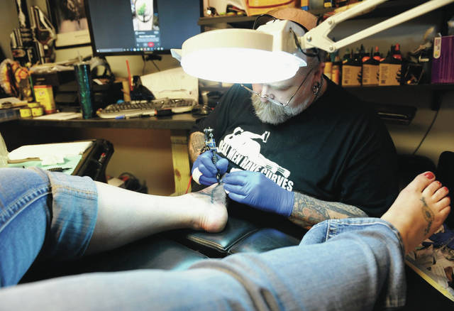 Jason Lawson, of Sidney, tattoos the image of a tree on the foot of Kim Campbell, of Piqua, at Bombshell Tattoo on Friday, May 15. Friday was the first day Bombshell Tattoo, owned by Lawson, has been able to reopen after being closed like the rest of the tattoo parlors in Ohio to prevent the spread of COVID-19.