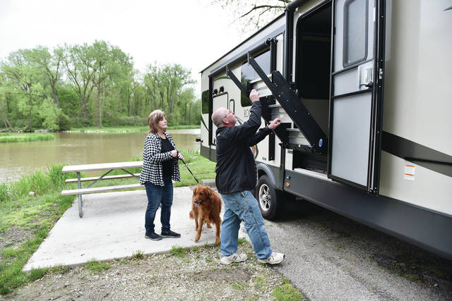 Darlene Mullen, left, watches as her husband, Kent Mullen, both of Sidney, unfolds the steps to their camper after arriving at the Lake Laramie State Park Campground on Thursday, May 21.