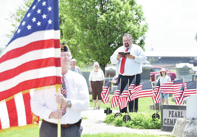Anna American Legion Post 446 member Larry Fultz, left, of Botkins, holds the U.S. flag while Pemberton Methodist Church Reverend Don Burley leads a Memorial Day ceremony at Pearl Cemetery, just south of Anna, on Monday, May 25. Anna American Legion Post 446 performed a rifle salute and Taps was played.
