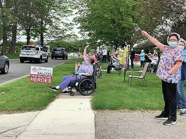 Residents and nurses from Sidney Care Center wave as a parade of well wishers go by on Friday, May 22. Nursing homes have been on lockdown because residents are susceptible to complications from COVID-19.
