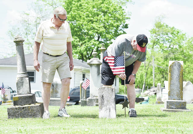 Tom Meyer, left, watches as Bob Barhorst, both of Fort Loramie, places a flag next to the grave of a U.S. veteran at Oran Cemetery on Sunday, May 24. The two Fort Loramie American Legion Post 355 members placed flags on all the graves of veterans buried in the cemetery in preparation for Memorial Day. Also with them was fellow Fort Loramie American Legion member Jim Eilerman.