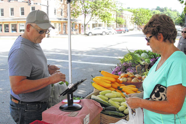 Jason Frantom, left, of Crossway Farms, 2211 Cisco Road, Sidney rings up a sale during a previous Great Sidney Farmers' Market. This year's market, held on the courtquare every Saturday morning from 8 a.m. until noon, opens Saturday and runs through Oct. 12. Matt Clayton | Sidney Daily News