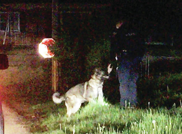 Sidney Police officers search for evidence at about 1:15 a.m. on Friday, May 1, along Foster Avenue near the corner of East Court Street. Photo courtesy Tony Heitmeyer