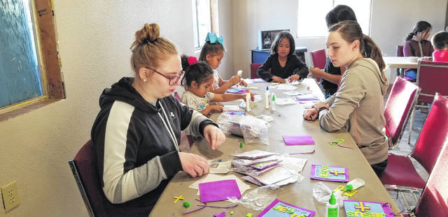 Alana Milks, left, and Emma Abbott, right, work on a craft project with students at the American Indian Christian Mission. Seniors at Christian Academy Schools traveled to Arizona at the beginning of March to serve at AICM as part of the school's annual mission trip.