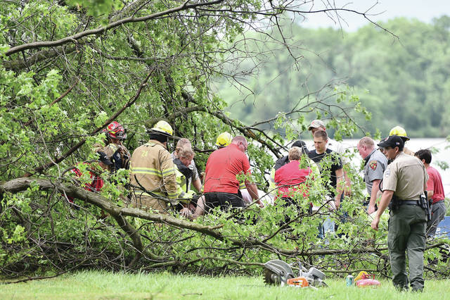 Fort Loramie firefighters and Fort Loramie rescue workers remove a man out from under the tree that fell on him at Lake Loramie State Park Campground on Wednesday, June 11.