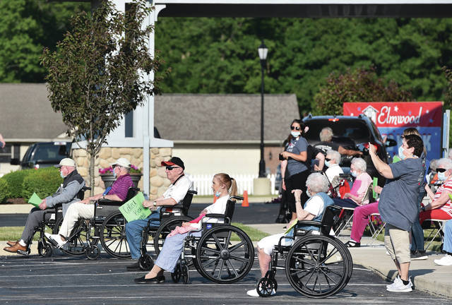 Residents of Elmwood of New Bremen, watch a parade of friends and family drive past on Tuesday, June 16.